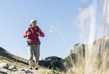 Austria, Tyrol, smiling woman on a hiking trip in the mountains - UUF16371