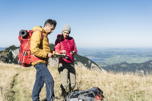 Austria, Tyrol, couple with map hiking in the mountains - UUF16392