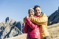 Austria, Tyrol, happy couple hugging on a hiking trip in the mountains - UUF16395