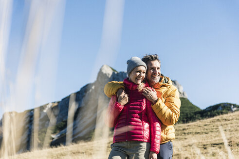 Austria, Tyrol, happy couple embracing on a hiking trip in the mountains - UUF16398