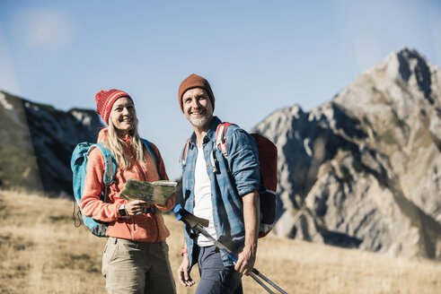 Austria, Tyrol, happy couple with map on a hiking trip in the mountains - UUF16404