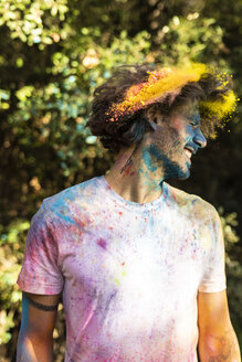 Man shaking his head, full of colorful powder paint, celebrating Holi, Festival of Colors - ERRF00472
