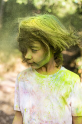Boy shaking his head, full of colorful powder paint, celebrating Holi, Festival of Colors - ERRF00481