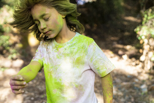 Boy shaking his head, full of colorful powder paint, celebrating Holi, Festival of Colors - ERRF00487