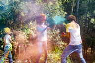 happy family celebrating Holi festival in the forest, throwing colorful powder paint - ERRF00499
