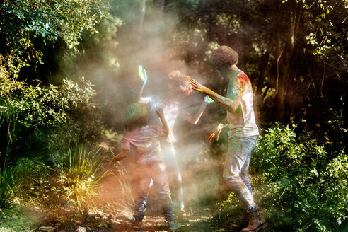 happy family celebrating Holi festival in the forest, throwing colorful powder paint - ERRF00502