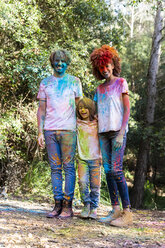 Family in the forest, full of colorful powder paing, after celebrating Holi, Festival of colors - ERRF00505