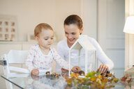 Mother and little daughter tinkering autumnal decorative house at home - DIGF05573