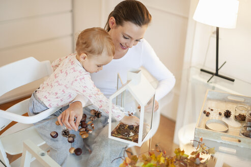 Mother and little daughter tinkering autumnal decorative house at home - DIGF05582