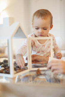 Mother and little daughter tinkering autumnal decorative house at home - DIGF05585