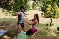 Female yoga teacher teaching young man yoga in garden, warrior pose - CUF46579