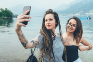 Girlfriends taking selfie by sea - CUF46648