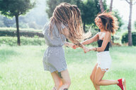 Girlfriends dancing in park - CUF46651