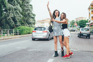 Girlfriends hailing cab in middle of road - CUF46654