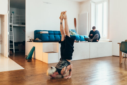 Woman practising yoga at home, friend in background - CUF46663