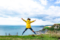 Boy jumping on clifftop by sea, Bournemouth, UK - CUF46726