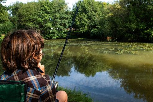Boy fishing by lakeside, Bournemouth, UK - CUF46729