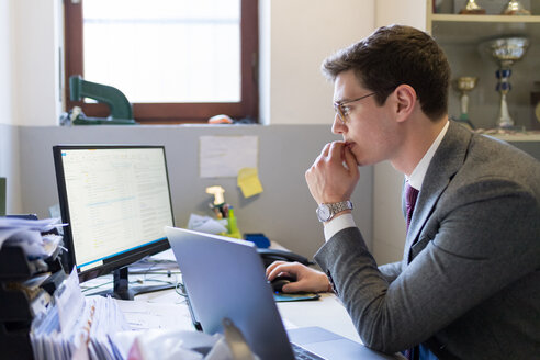 Man using laptop and desktop in office - CUF46732