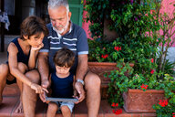 Grandfather sitting with grandsons on front door steps - CUF46813