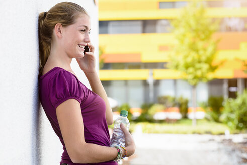 Young woman talking on smartphone in park - CUF46888