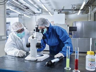 Industriefotografie (mit Release) Chemikerin und Chemikerin mit weißen und blauen und Schutzanzügen, Haarnetzen und Atemschutzmasken arbeiten im Reinraum, Wattens, Tirol, Austria - CVF01110