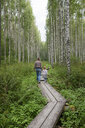 Finland, Kuopio, mother and daughter walking in a birch forest - PSIF00208