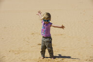 Spain, Canary Islands, Fuerteventura, Parque Natural de Corralejo, playful girl in sand dunes - RUNF00865