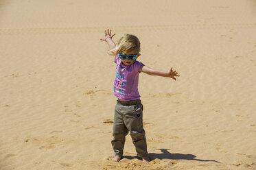 Spain, Canary Islands, Fuerteventura, Parque Natural de Corralejo, playful girl in sand dunes - RUNF00865