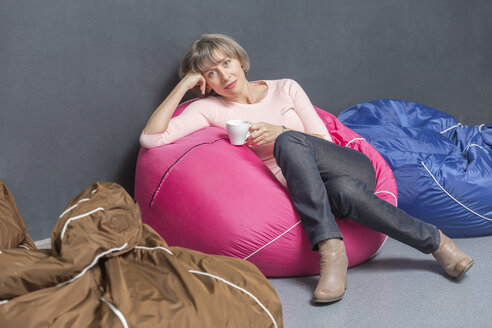 Portrait of woman relaxing with cup of coffee on bean bag in the office - VGF00170