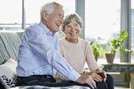 Portrait of laughing senior couple sitting together on couch - RBF06983