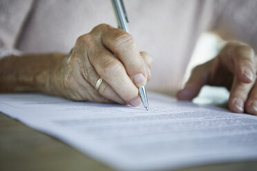 Senior woman's hand signing a document, close-up - RBF06989