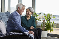 Laughing senior couple sitting together on couch - RBF06992