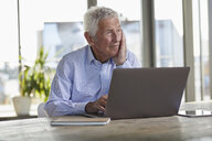 Portrait of pensive senior man sitting at table with laptop looking at distance - RBF07004