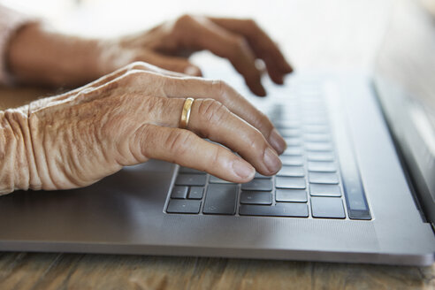 Hand of senior woman typing on keyboard of laptop, close-up - RBF07007