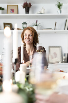 Portrait of a readheaded woman sitting at a dinner party - ERRF00557