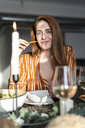 Portrait of a readheaded woman sitting at a dinner party - ERRF00560