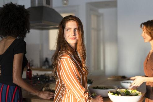 Friends standing in kitchen, preparing a dinner party - ERRF00590