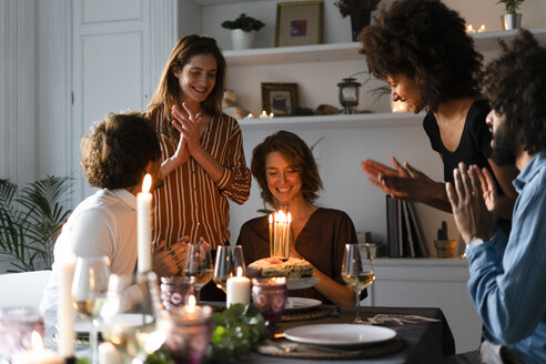 Friends surprising young woman with a birthday cake with burning candles - ERRF00596