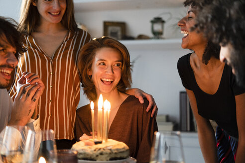 Friends surprising young woman with a birthday cake with burning candles - ERRF00599