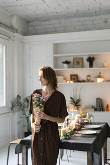 Redheaded woman holding bunch of flowers, standing in front of laid table - ERRF00608