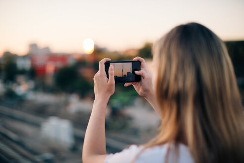Young woman photographing Fernsehturm through smart phone during sunset - MASF10317