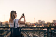 Young woman photographing through mobile phone while standing on bridge against clear sky during sunset - MASF10323