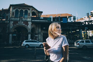Young woman looking over shoulder while holding mobile phone on street in city - MASF10383
