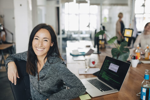 Portrait of smiling female computer programmer sitting at desk in creative office - MASF10389