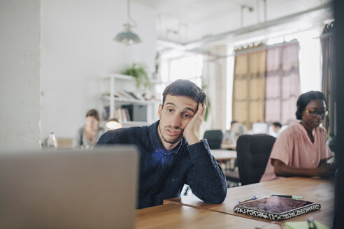 Tired businessman looking at laptop while sitting at desk in creative office - MASF10401