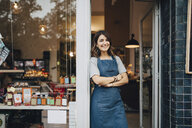 Portrait of confident female owner standing at entrance of deli - MASF10551