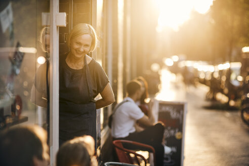 Portrait of smiling female employee standing at entrance of deli - MASF10554