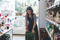 Female employee removing bottle from crate while standing in deli - MASF10566