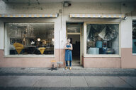 Portrait of confident male upholstery worker standing at workshop entrance - MASF10611