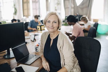 Portrait of confident mature businesswoman sitting at computer desk in creative office - MASF10665